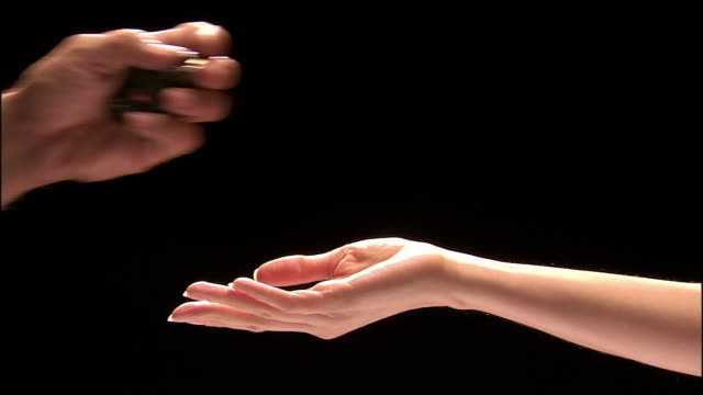 close up studio shot of man's hand placing keys in woman's palm / woman's hand clasping keys - giving stock videos and b-roll footage
