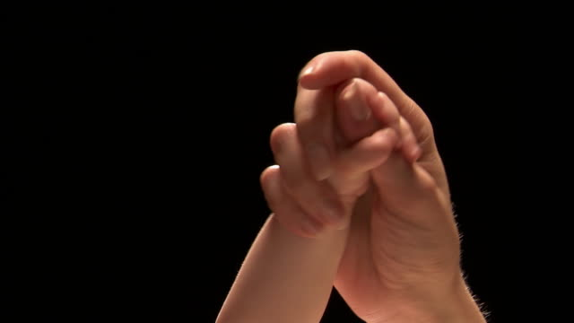 Close up studio shot of mother's hand holding baby's hand (baby's hand clasping mother's thumb)