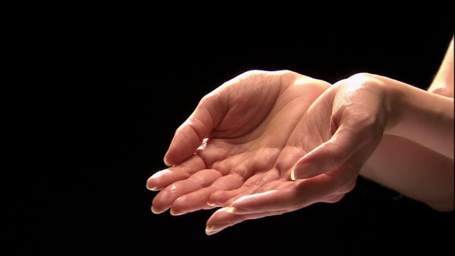 vidéos et rushes de close up studio shot of woman's cupped hands / folding palms together - donner