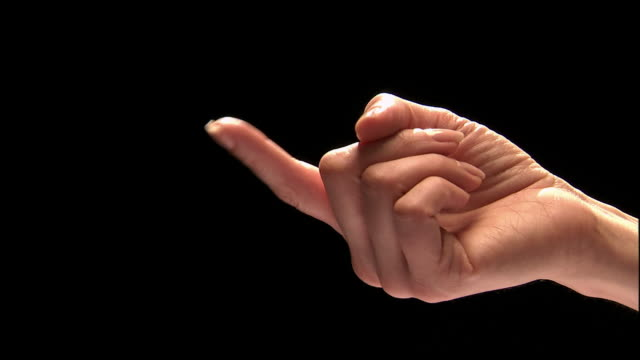 Close up studio shot of woman's hand giving beckoning sign