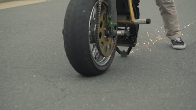 slo mo. cu . close- up. stunt motorcycle rider stands on the back of his bike while doing a wheelie on an empty street on an overcast winter day - stunt stock-videos und b-roll-filmmaterial
