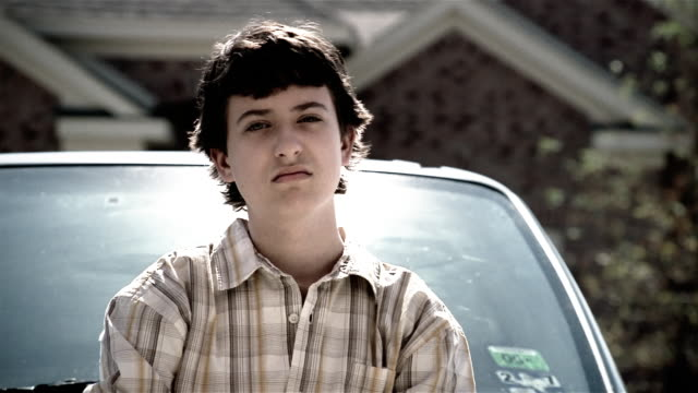 Close up sullen teenage boy leaning on minivan in driveway of suburban home