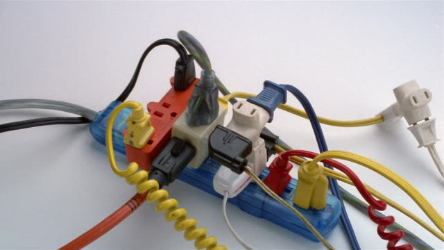 close up surge protector overloaded with plugs / hand plugging in another cord - electrical plug stock videos & royalty-free footage