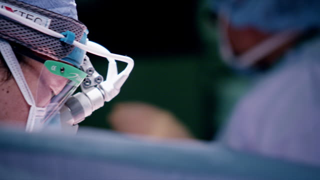 vidéos et rushes de close up, surgeons perform procedure in hospital operating room - bloc