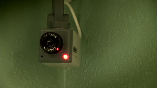 vidéos et rushes de close up surveillance camera moving back and forth / flashing light - surveillance