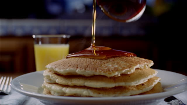 close up syrup being poured on stack of steaming buttered pancakes - pancake stock videos & royalty-free footage