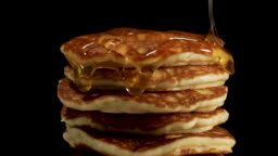 Close up Syrup flows down on a pile of pancakes