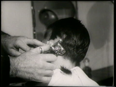 B/W 1951 REAR VIEW close up teen boy getting back of head shaved in barbershop / France / newsreel
