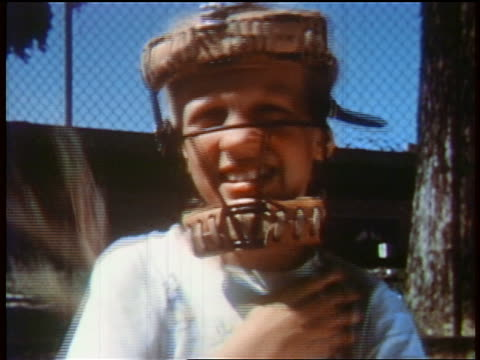 stockvideo's en b-roll-footage met 1957 close up teen girl in catcher's mask pushes braids back + raises baseball glove / educational - 1957