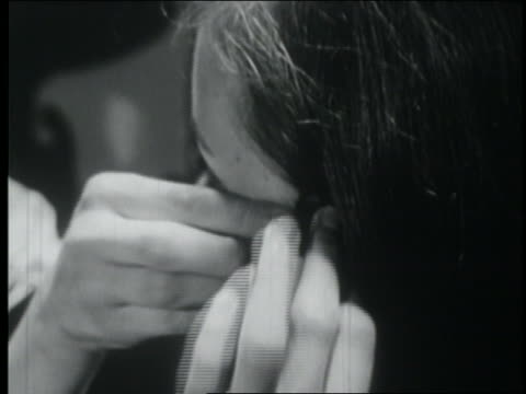vídeos de stock, filmes e b-roll de b/w 1953 close up teen girl putting bobby pins in her hair - only teenage girls