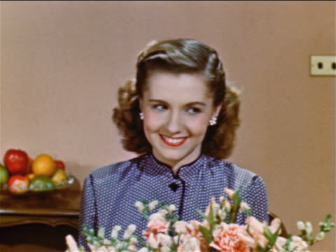 1952 close up teen girl sitting behind flower arangement looking at someone off screen + smiling / indust. - 1952 stock videos & royalty-free footage