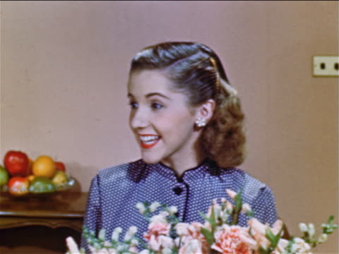 1952 close up teen girl sitting behind flowers talking to someone off screen / industrial - 1952 stock videos & royalty-free footage