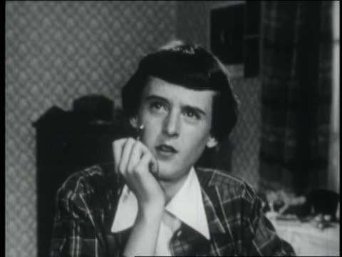 b/w 1953 close up teen girl with short hair sitting with pen + thinking / gets up + exits - solo adolescenti femmine video stock e b–roll
