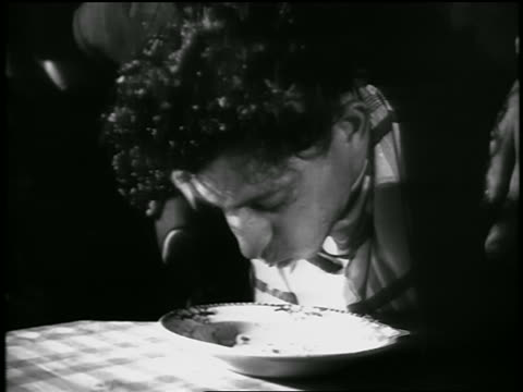 stockvideo's en b-roll-footage met b/w close up teenage boy eating spaghetti w/out hands in contest / finishes as people behind him cheer - alleen één tienerjongen