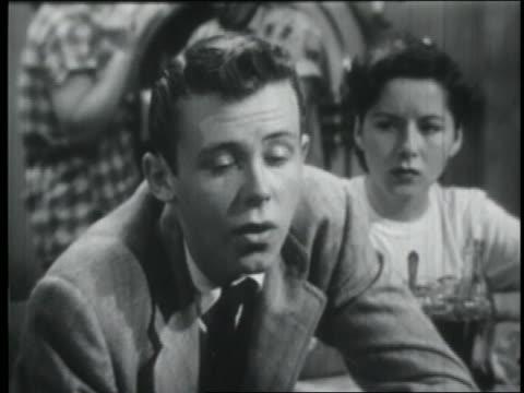 vídeos de stock e filmes b-roll de b/w 1951 close up teenage boy talking / jealous girlfriend in background - 1951