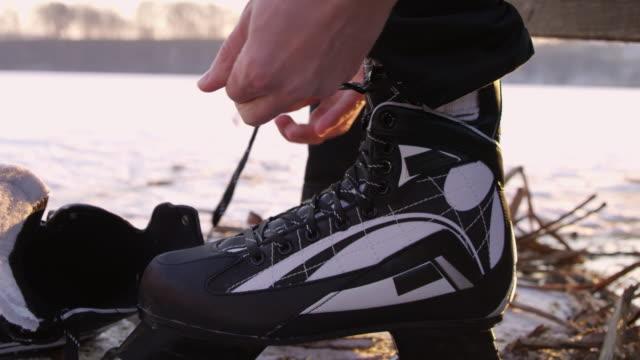 4K Close up teenage boy tying ice skate shoelace, slow motion