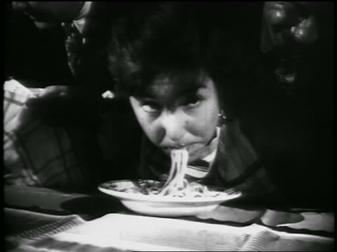 B/W close up teenage girl eating spaghetti w/out hands in contest