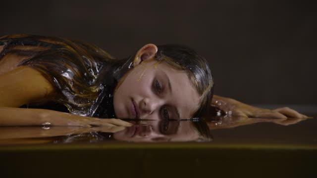 close up, teenage girl lies in honey - one teenage girl only点の映像素材/bロール