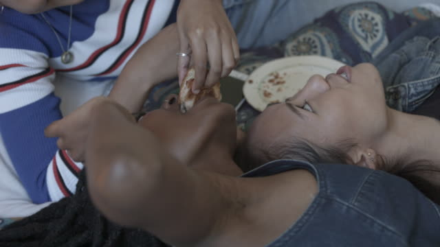close up, teenagers laugh at eat on bed in slow motion - liegen stock-videos und b-roll-filmmaterial