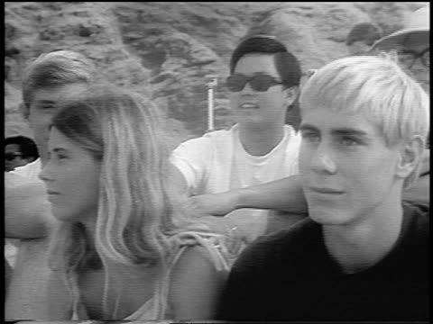 b/w 1966 close up teens on beach watching offscreen surfing competition / hawaii / newsreel - 1966 stock videos and b-roll footage