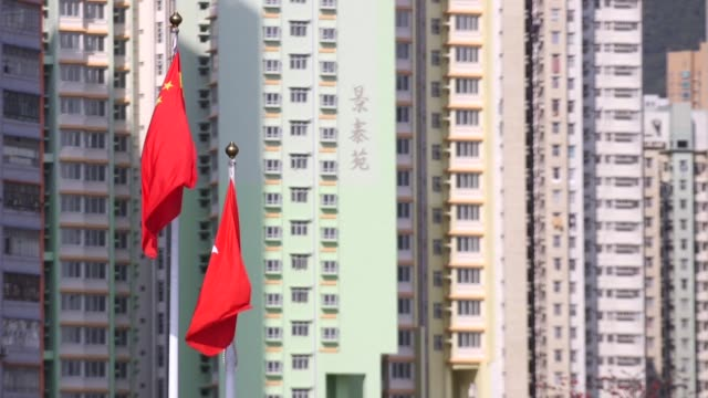 close up, the chinese national flag, left, and the hong kong flag fly in front residential buildings at the former kai tak area of hong kong, china,... - hong kong flag stock videos & royalty-free footage