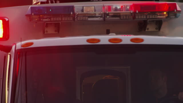"close up the top front of an emergency ambulance lights flashing in the early evening light as it drives past camera and reveals a hospital's ""emergency"" sign. - televisione a ultra alta definizione video stock e b–roll"