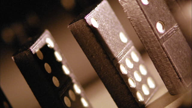 tinted canted close up three dominoes falling in line - dominoes stock videos & royalty-free footage