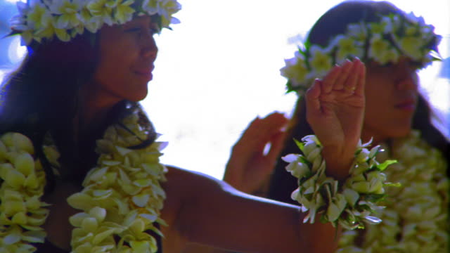 close up pan three female hula dancers in leis doing arm movements in unison / ocean in background / hawaii - hawaiian ethnicity stock videos & royalty-free footage