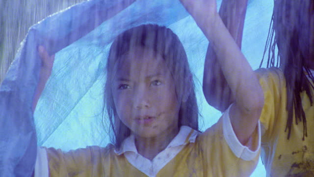 close up pan three girls in muddy soccer uniforms standing under tarp in heavy rain - mud stock videos & royalty-free footage