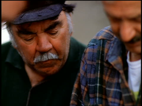 vidéos et rushes de close up three greek men looking down while stringing piece of lamb (not visible) / greece - moustache