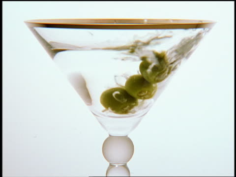 close up three olives on toothpick dropping in martini glass / white background - martini glass stock videos and b-roll footage