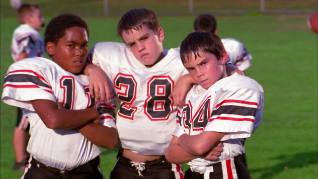 Close up three young boys in football uniforms looking seriously at CAM