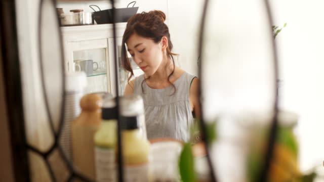 vídeos de stock, filmes e b-roll de feche acima através de um indicador de uma mulher nova que cozinha - almoço