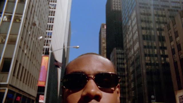 close up tilt down black businessman in sunglasses on street / nyc - occhiali da sole video stock e b–roll