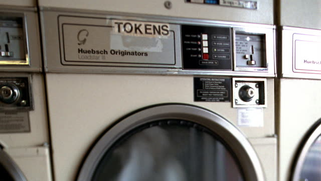 close up tilt down clothes dryer in laundromat with clothes spinning / los angeles, california - launderette stock videos & royalty-free footage