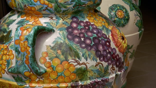 Close up tilt down detail of white and red grape design on ceramic pitcher or vase / Praiano, Amalfi Coast, Italy