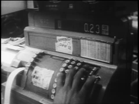 stockvideo's en b-roll-footage met b/w 1962 close up tilt down from cashier's hand on cash register to groceries on conveyor / cuban missile crisis - koude oorlog