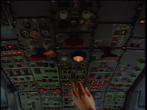 close up tilt down from ceiling of airliner cockpit with hands of male pilot + co-pilot hitting controls / Toronto