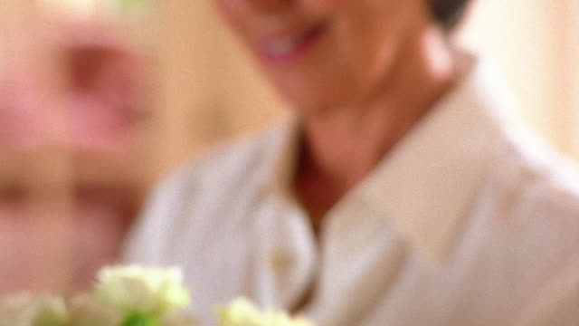 close up tilt down from face (out of focus) of middle age woman to bouquet of pale pink roses she is arranging