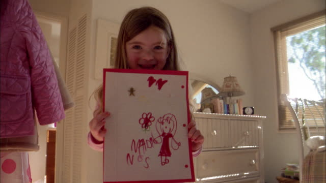 close up tilt down girl smiling and holding up homemade drawing to cam - human face drawing stock videos & royalty-free footage