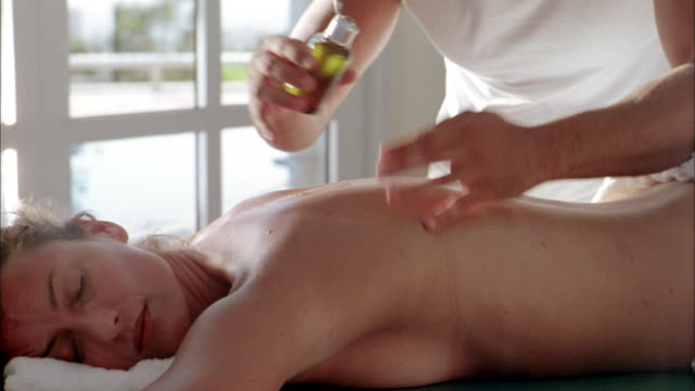 vídeos de stock e filmes b-roll de close up tilt down male masseur pouring massage oil and massaging woman's back - cara para baixo