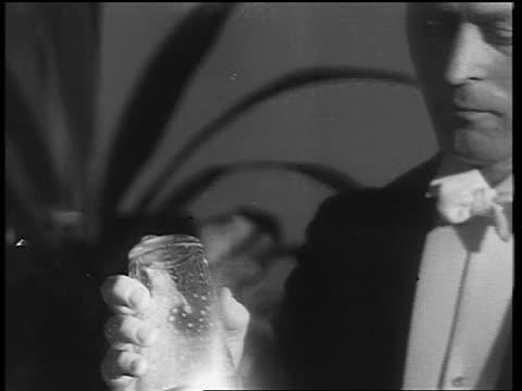 b/w 1933 close up tilt down man in formalwear shaking drink in cocktail shaker / end of prohibition - 1933年点の映像素材/bロール