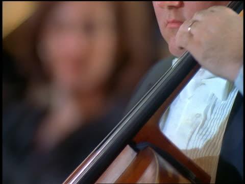 vídeos de stock e filmes b-roll de close up tilt down man playing cello in orchestra - só homens maduros