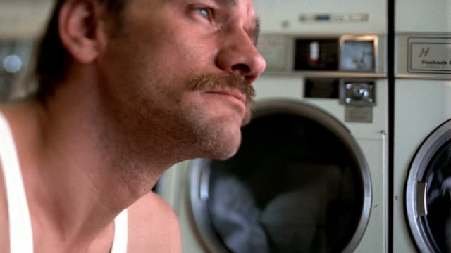 stockvideo's en b-roll-footage met close up tilt down pan from man looking serious to row of dryers with clothes spinning in background / los angeles, ca - profiel