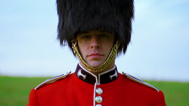 close up tilt down portrait buckingham palace guard / zoom in to face / grass in background / london, england - 近衛兵点の映像素材/bロール