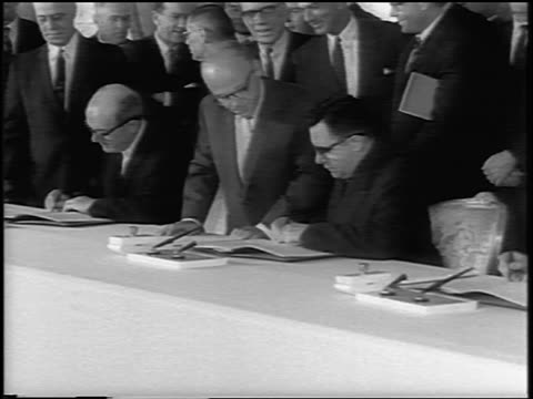 B/W 1963 close up tilt down PROFILE Andrei Gromyko in eyeglasses signing Atomic Test Ban Treaty / newsreel