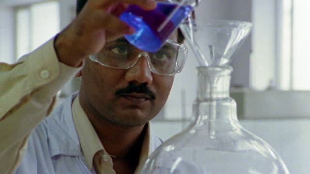close up tilt down research scientist wearing goggles pouring blue liquid into large beaker / india - south asia stock videos & royalty-free footage