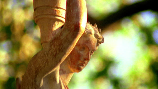 close up tilt down roman style statue of woman wearing robe and holding jar outdoors / provence, france - traditional clothing stock videos & royalty-free footage