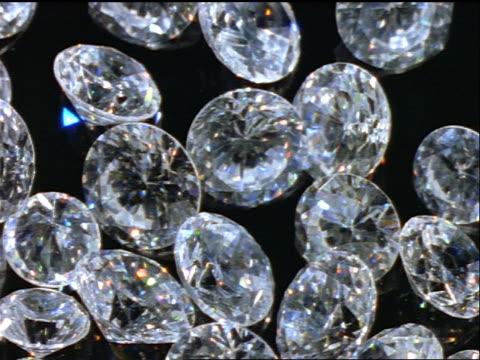 vidéos et rushes de overhead close up tilt down round + oval cut diamonds on black surface - diamant