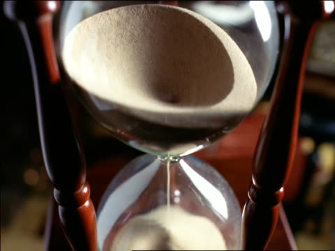 close up tilt down sand running through hour glass - hourglass stock videos & royalty-free footage